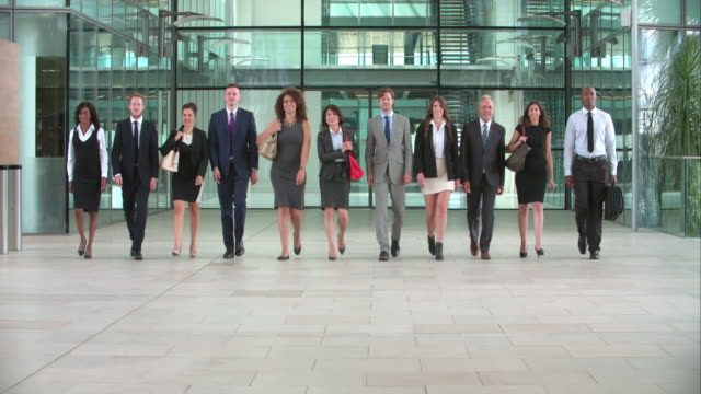 Business colleagues walking towards camera in a modern foyer video