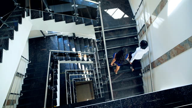 Business couple walking up stairs together. The view from the top video