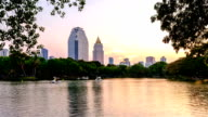 Business district cityscape from a park with Twilight Time from Lumpini Park, Bangkok, Thailand video