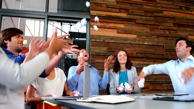 Business executives throwing crumpled paper in air video