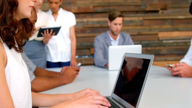 Business executives using laptop in office video