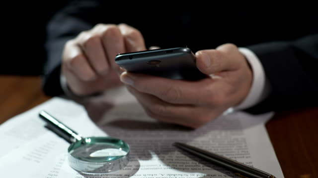 Business expert scrolling financial news feed on smartphone, working on contract video