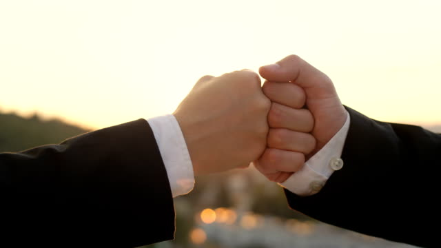 CLOSE UP: Business fist-bump at sunset with beautiful cityscape in background video