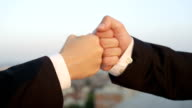 CLOSE UP: Business fist-bump with beautiful view of cityscape in the background video