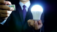 Business idea and vision, businessman holding shining light bulb, concept of new ideas, innovation, invention and creativity. video