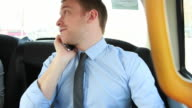 Business male in back of cab on the phone video
