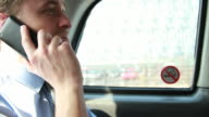 Business male in back of Taxi on the phone video