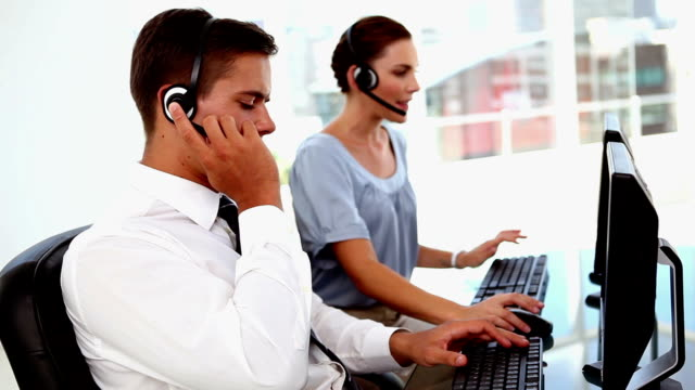 Business man and business woman in a call centre video