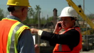 Business man and construction worker talking on site video