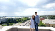 Business man and woman are standing on roof posing video