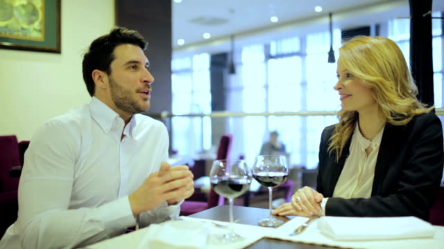 Business man and woman drinking wine after luch video