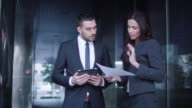 Business Man and Woman Having Meeting and Conversation Outdoor. Businessman Holding and Using Tablet While Talking. video