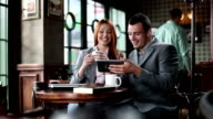 Business man and woman in cafe using digital tablet. video