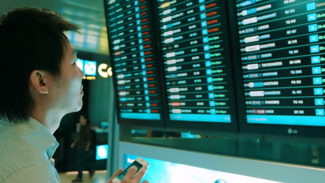 Business man at airport check depatures board video