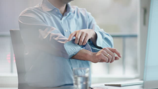business man at office desk rolling up sleeves video