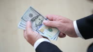 Business man counting 100 dollar bills video