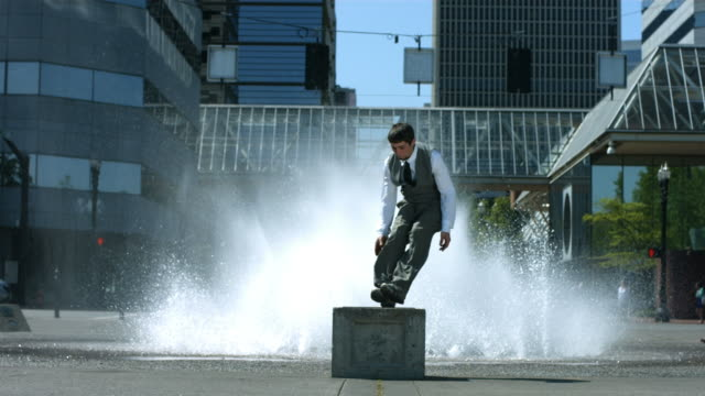 Business man does flip in front of city fountain video
