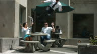Business man flips off courtyard table video