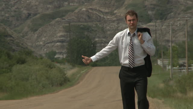 Business man hitch hiking on a lonely country road video