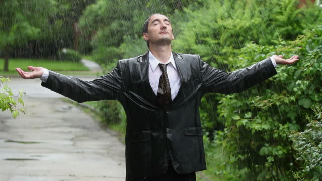 Business man in rain, holding up arms video