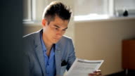 Business man is reading document sitting in office video