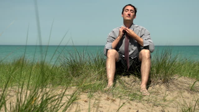 Business man loosening his tie on the beach video