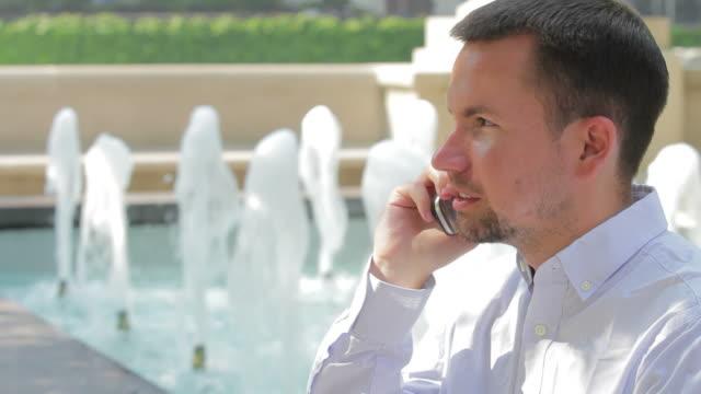 Business man on the phone near a fountain video