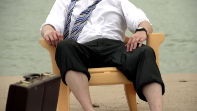 Business man relaxing on the beach video