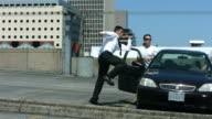Business man runs through parking lot jumping over car video