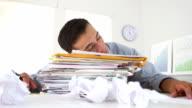 Business man sleeping on stack of paperwork video