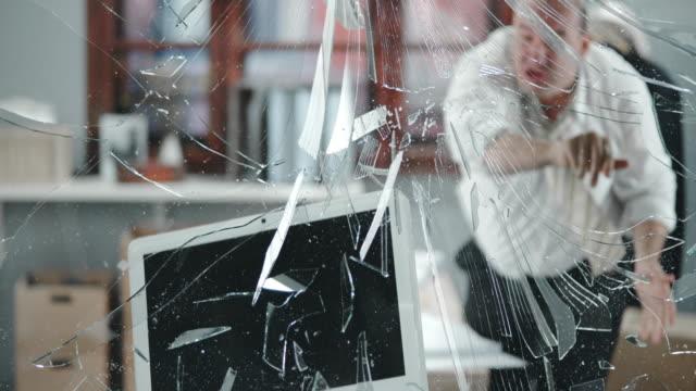 SLO MO Business man throws his computer through the window video