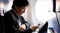 business man using tablet on the plane video