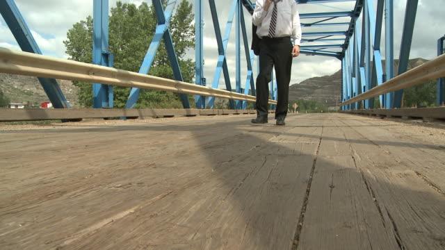 Business man walks across a bridge video