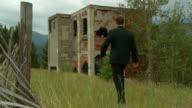 Business man walks toward abandoned building video