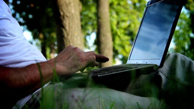 Business man working on a notebook in the park. video
