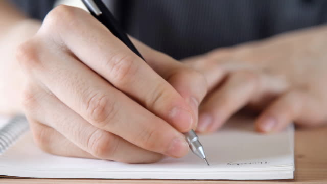 business man writing on the notebook - close up view video
