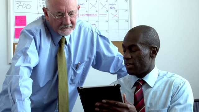 Business men meeting and looking at tablet video
