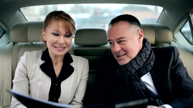 Business partners talking in the backseat of a car video