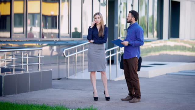 Business people are working outside. Female sales manager standing near office speaking on the telephone. Man dressed in blue shirt and brown trousers is listening to businesswoman and making notes video