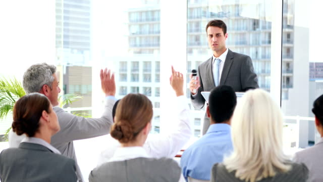 Business people asking question during presentation video