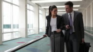 Business people at airport travel on moving walkway video