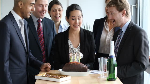Business people celebrating birthday in office video