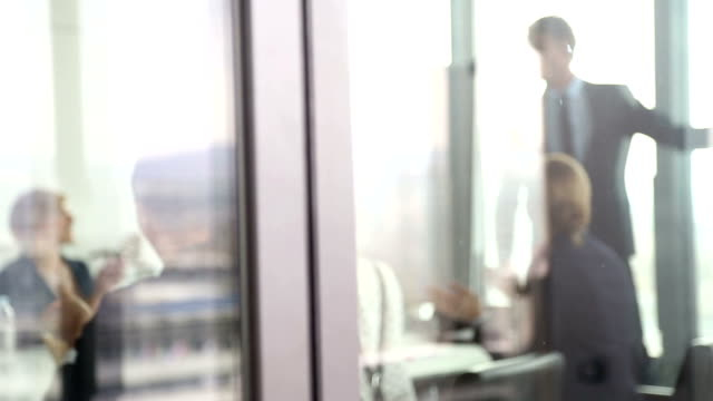 Business people clapping to colleague in conference room, behind glass wall video