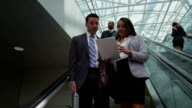 Business people going down escalator video