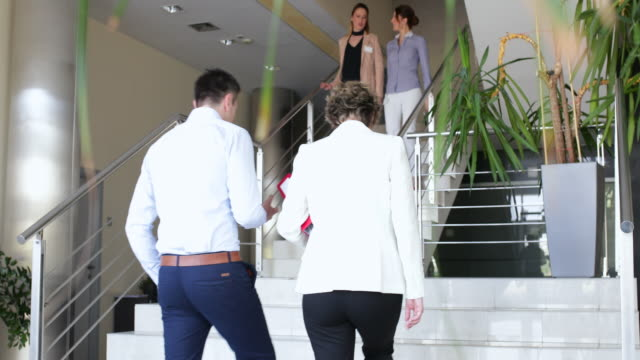 Business people greeting each other on the stairs video