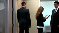 Business people in an office setting talking together. video