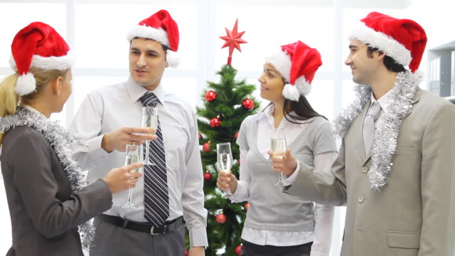 Business people in Santa cap holding flutes with champagne. video
