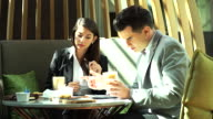 Business people interacting with there document information during meeting at coffee shop. video