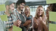Business people looking at sticky notes. Good news. video