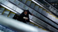 Business people on escalator, overhead view video